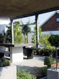Peter Englander Pergola med vasstak skapar skugga över middagsterrassen i slipad betong.