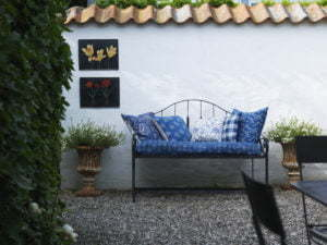 Peter Englander Bakplåtskonst på vit mur, smidessoffa med vackra kuddar.