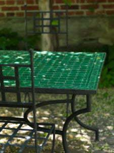 Peter Englander Mörkt grönt mosaikbord i fladdrande pergolaskugga.