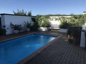 Peter Englander Pool med hög mur, upphöjda odlingsbäddar och tegelterrass.